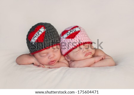 "Five week old sleeping boy and girl fraternal twin newborn babies. They are wearing crocheted ""Love Mom"" and ""Love Dad"" beanies. - stock photo"