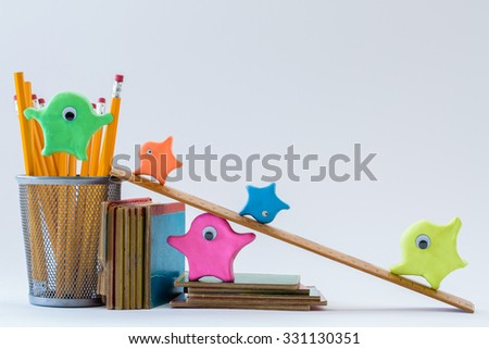 Five whimsical, multicolored playdough monster people playing on school supplies to have an educational adventure. Great for teaching children of all ages, nationalities, and for multicultural uses. - stock photo
