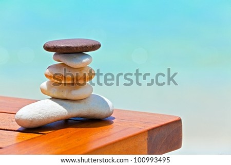 Five white and brown stones are on  beach table - stock photo