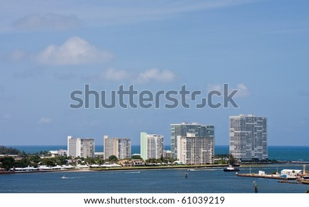 Five white condo towers on the coast by a shipping channel