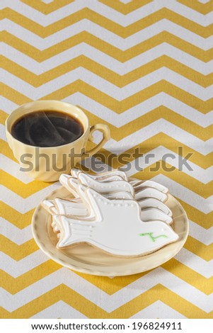 Five white (dove shaped) Cookies on yellow plate with steaming coffee - stock photo