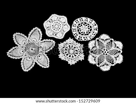 Five white vintage crocheted mats on a black background - stock photo