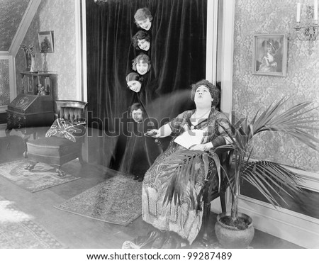 Five woman looking at one woman from behind a curtain - stock photo