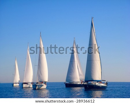 five yachts sail in the blue sea - stock photo