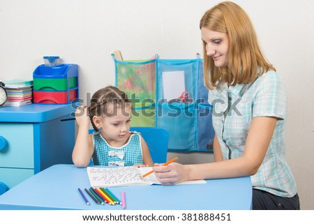Five-year girl draws pencil in a notebook and looked into the frame - stock photo