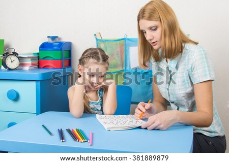 Five-year girl with interest looks at the teaching material explained by an adult - stock photo