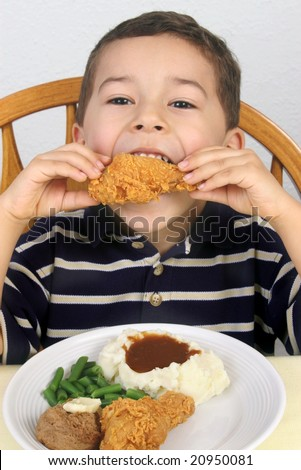 five-year-old boy eating fried chicken - stock photo