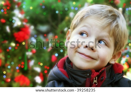 Five year old boy portrait outside with decorated Christmas trees - stock photo