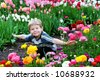 Five year old boy surrounded by colorful spring flowers - stock photo