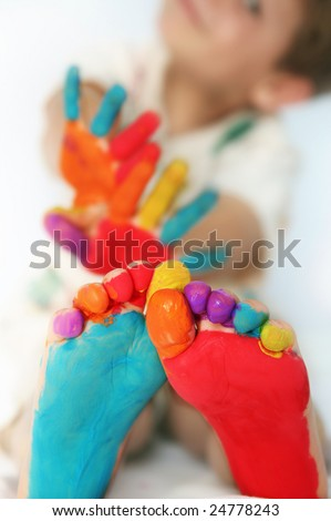Five year old boy with feet and hands painted. Shallow DOF with focus on feet. - stock photo