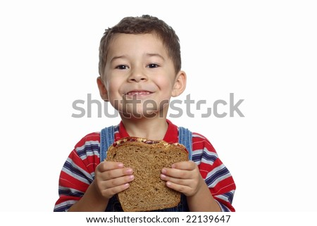 five-year-old boy with peanut butter and jelly sandwich - stock photo