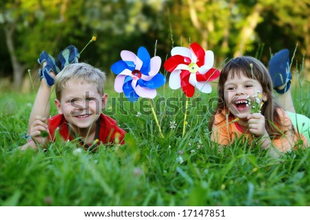 Five year old friends laying in a grass with colorful pinwheels - stock photo