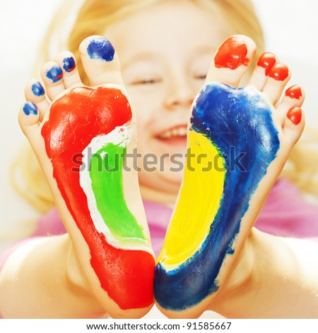 Five year old girl with feet painted.  with focus on feet - stock photo