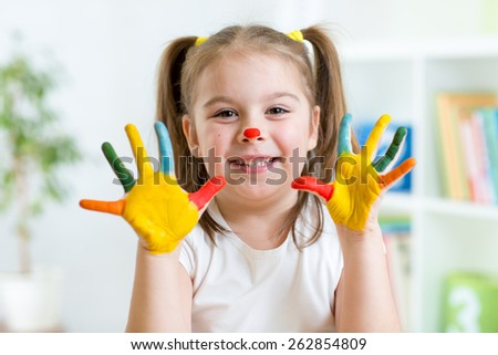 Five year old girl with hands painted in colorful paints over playroom background - stock photo