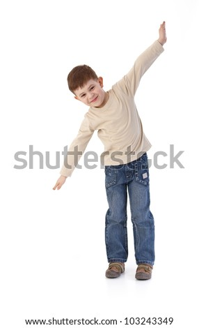 Five year old little boy imitating flying as an airplane, smiling. - stock photo