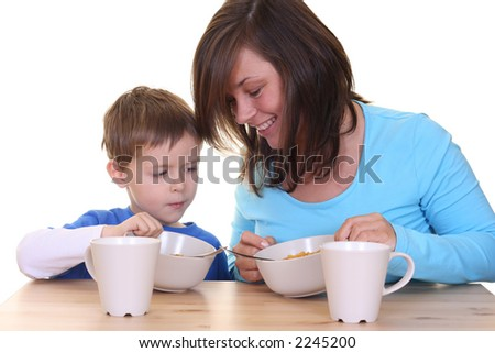 five years boy and his mother - breakfast together- isolated on white