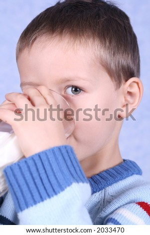 five years boy drinking milk blue background