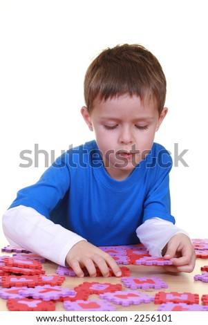 five years boy playing with letters isolated on white