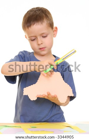 five years old boy cutting papper isolated on white