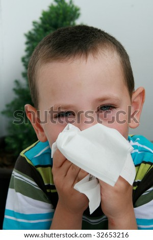 Five years old boy with tissue blowing his nose. Child with allergy, conjunctivitis and black rings round his eyes. - stock photo