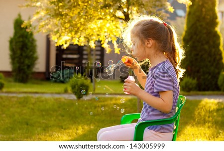 Five years old caucasian child girl blowing soap bubbles outdoor at sunset - stock photo
