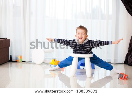 five years old child laughing in the living room or kindergarten, a happy kid playing like an airplane - stock photo