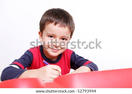 Five years old child writing, White background, Child is smiling and looking at camera - stock photo