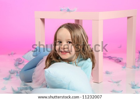 Five years old girl having fun with blue pillows and feathers at small table on pink colored background.