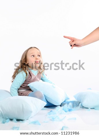 Five years old girl having fun with blue pillows and feathers on white background. Being told by mom to stop. - stock photo
