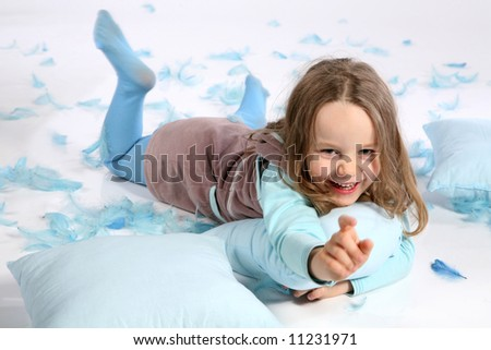 Five years old girl having fun with blue pillows and feathers on white background. Pillow fight !