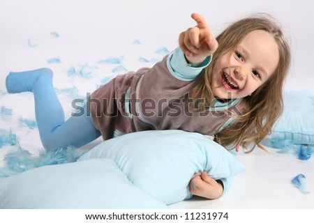 Five years old girl having fun with blue pillows and feathers on white background. Pillow fight ! - stock photo