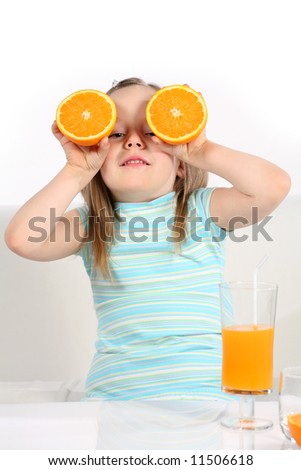 Five years old girl looking through oranges.