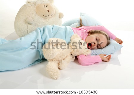 Five years old girl sleeping with her small friends. Studio shot on reflective floor. - stock photo