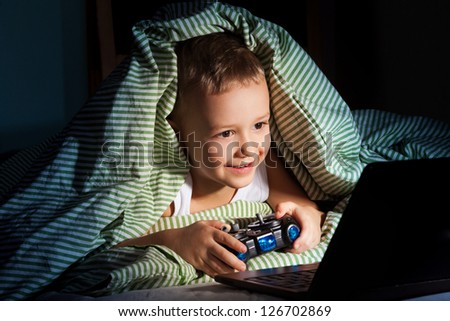 five years old happy kid hiding under blanket playing computer games - stock photo