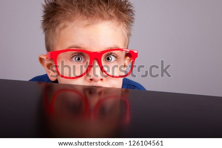 Five years old little cute boy hiding behind a table