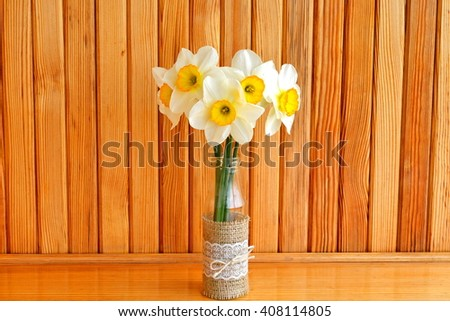 Five yellow daffodils in a vase. Wooden background  - stock photo