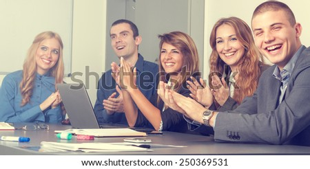 Five young business people at the end of a successful meeting applauding - stock photo