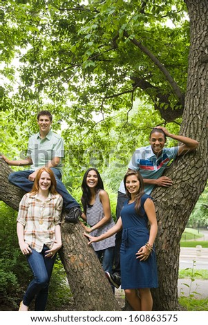 Five young friends around tree