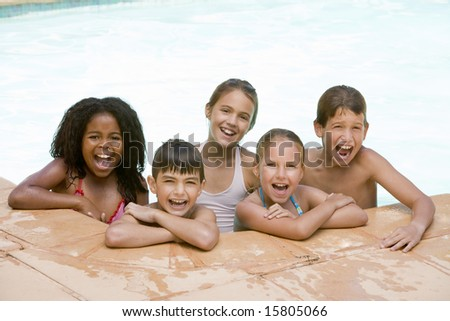 Five young friends in swimming pool smiling - stock photo