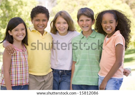 Five young friends standing outdoors smiling - stock photo