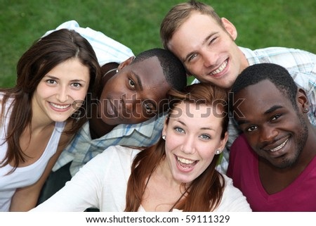 Five young, happy people from different countries laughing towards the camera
