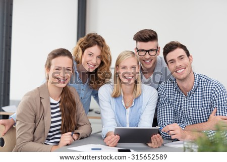 Five Young Office Workers in Casual Clothing, Sitting Inside the Boardroom, Smiling at the Camera. - stock photo