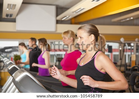 five young people training on treadmills at gym - stock photo