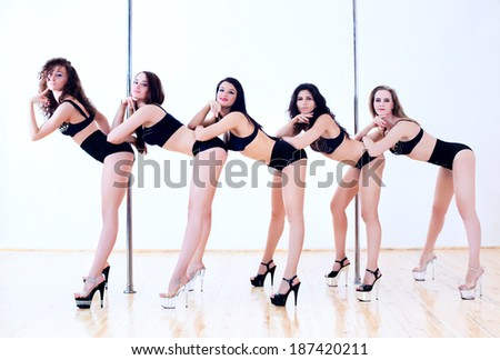 Five young pole dance women. - stock photo