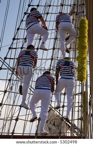 five young sailor climb on a school ship - stock photo