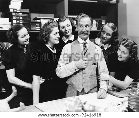 Five young women gathering around a salesman in a store - stock photo
