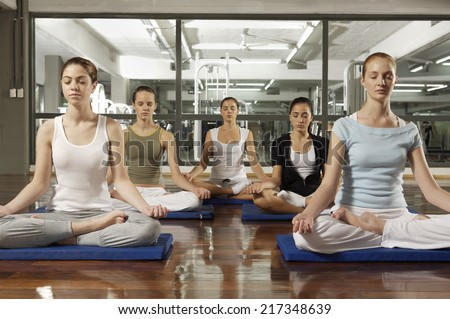 Five young women meditating in a gym - stock photo