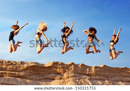Five young women on beach. - stock photo