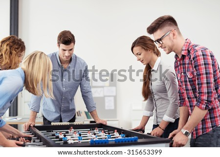 Five Young Workmates Playing Table Soccer Game Seriously in the Office During Free Time. - stock photo