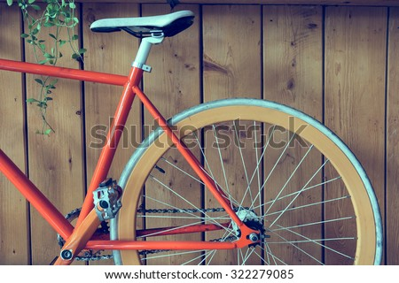 fixed gear bicycle parked with wood wall, close up image part of bicycle - stock photo